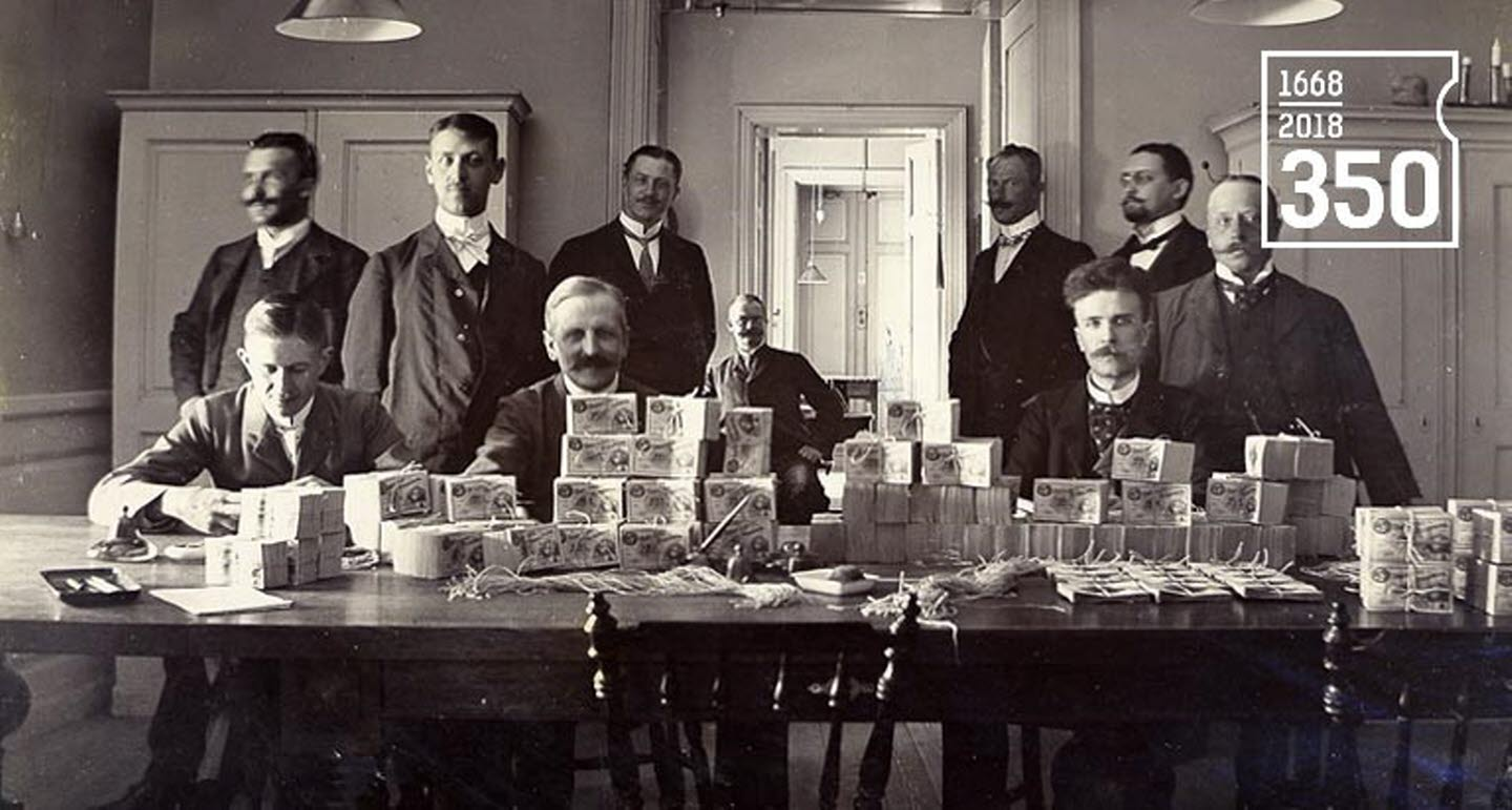 Counting banknotes at the Riksbank's banknote office at Järntorget on 17 June 1904, with the Riksbank 350 years logotype